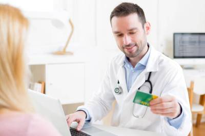 doctor taking health insurance card to patient