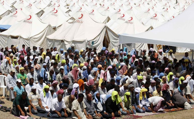 Syrian refugees attend Friday prayers at a refugee camp in the Turkish border town of Boynuyogun in Hatay province