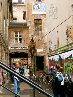 A backstreet area with a cafe, stores, and artwork on the walls