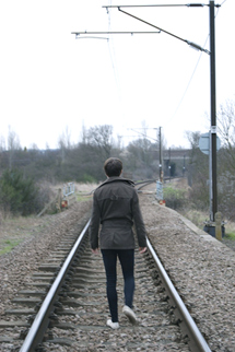 A young man walking on the railroad tracks