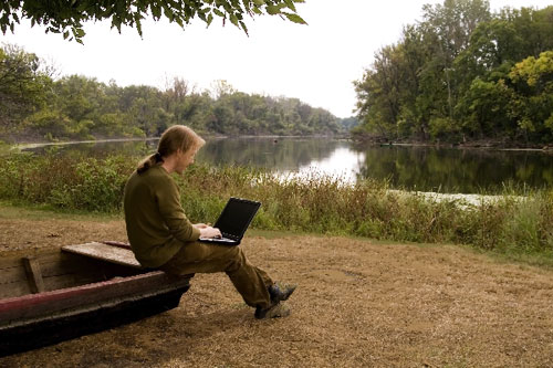 Guy using a laptop by the side of a river.