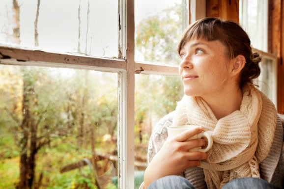 Young woman with Tea Gazing Out Window