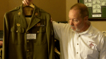 Ernie Scarano holds WWII uniform once belonging to Ohio artist Clyde Singer