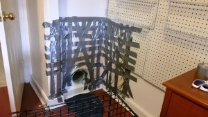 Plate 9: Repositioned cat baffle, with sufficient duct tape in place to prevent feline-induced pulldown.