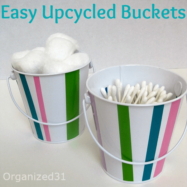 2 white and striped buckets holding cotton swabs and cotton balls