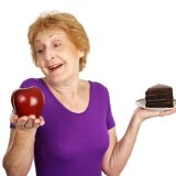 Fit senior lady choosing a healthy apple for dessert instead of fattening chocolate cake. Isolated on white.