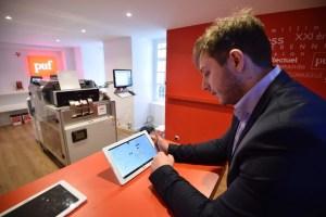 Alexandre Gaudefroy, gerente da livraria, e os tablets que permitem a consulta dos títulos à venda.