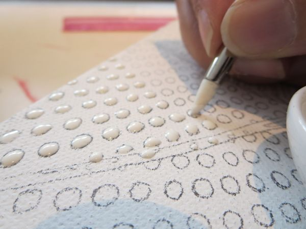 applying masking fluid on canvas