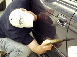 technician performing paintless dent repair on an automobile in Columbus Minnesota