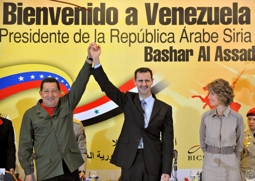 Syrian First lady Asma al-Assad looks on as Venezuelan President Hugo Chavez (L) and his Syrian counterpart Bashar al-Assad raise their arms together during a meeting with the Venezuelan Arab community in Caracas on June 27, 2010. AFP PHOTO/SANA/HO -- RESTRICTED TO EDITORIAL USE -- (Photo credit should read -/AFP/Getty Images)