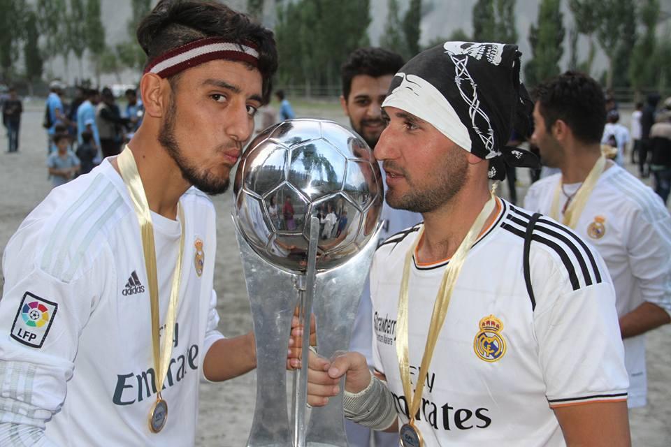 Winning players rejoice kissing the trophy, Photo: Rehmat Jabbar