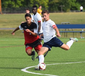 Hill School's Jake Fetterman sends the ball long under pressure from Germantown Academy's Michael Capone Wednesday. (Austin Hertzog - Digital First Media)