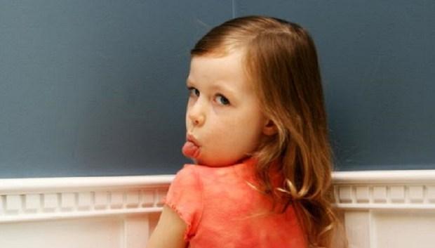 la punition est inefficace : la petite fille au coin tire la langue