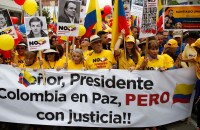 Colombian opposition led by former President Alvaro Uribe march to protest against President Juan Manuel Santos' government and denounce concessions they have made in peace talks with the Revolutionary Armed Forces of Colombia, or FARC,  in Bogota, Colombia, Saturday, April 2, 2016. (AP Photo/Fernando Vergara)