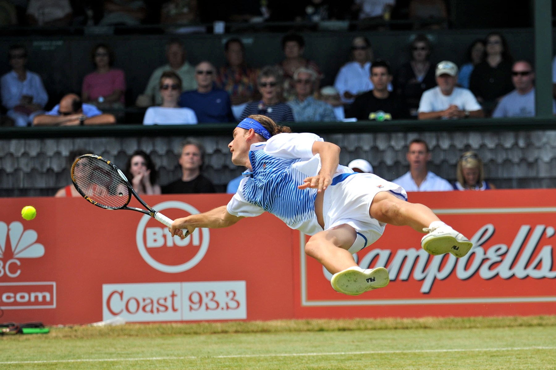 Dancevic dives on the grass at the International Hall of Fame in Newport, Rhode Island, USA.