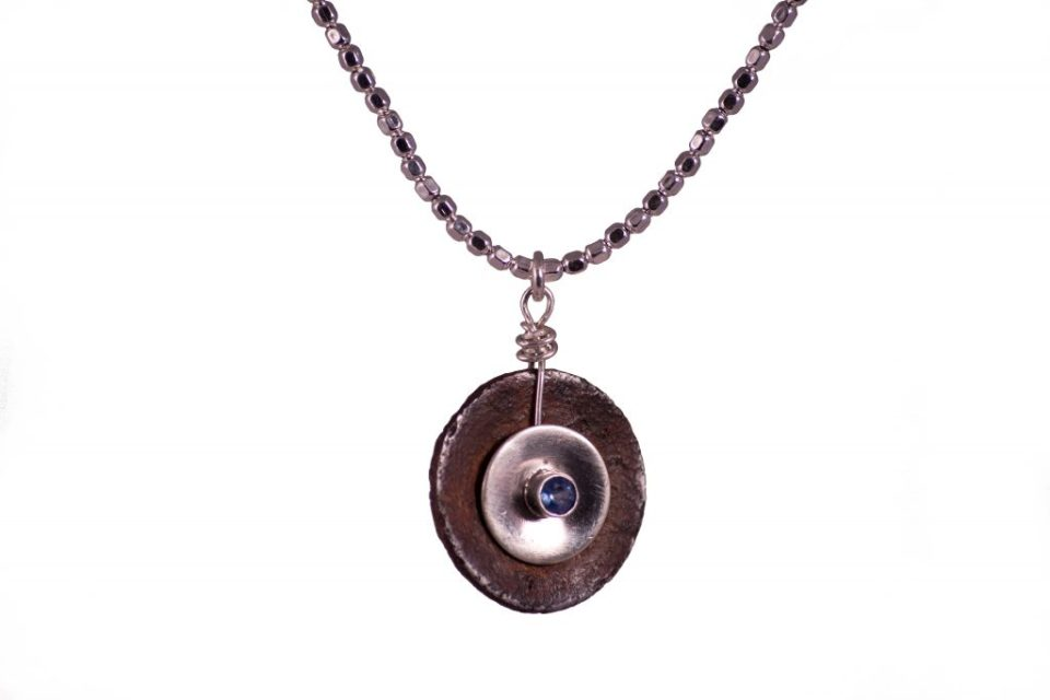 Rusted washer set with silver and sapphire.