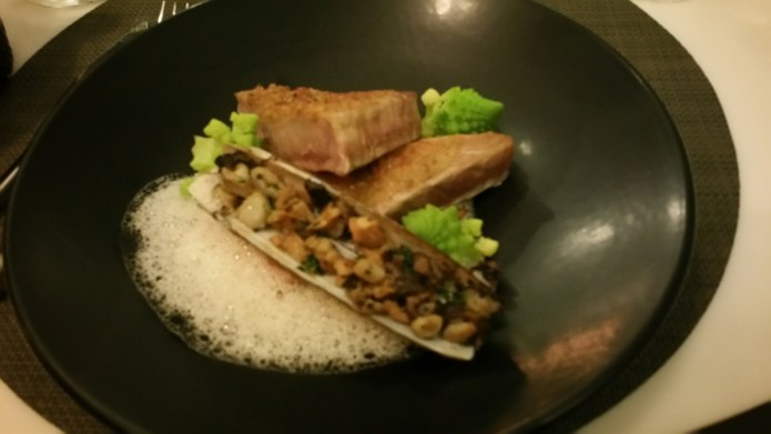 Tuna crusted with walnuts on a bed of shitaki mushrooms served with diced razor clam