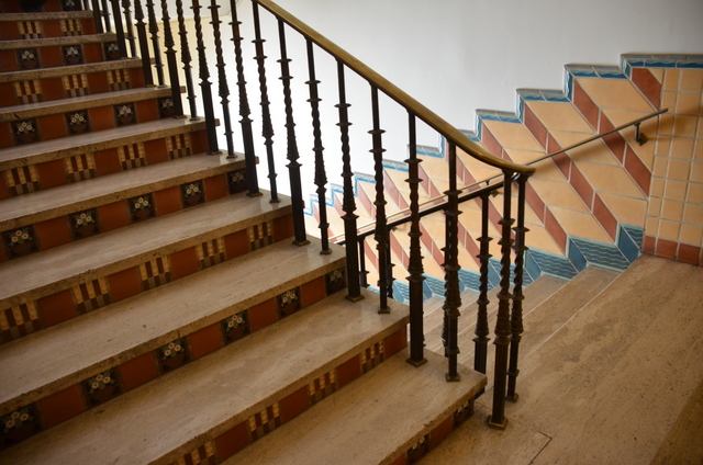 The stairways and walls are tiled, and the brass railings ornamented