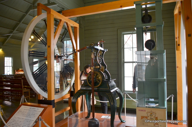The clock in the tower was built by E. Howard & Co. from Boston and it is a weight driven clock. That means a large weight, 50kg in this case, is suspended from the clock and descends under the force of gravity at a calculated rate. When the weight reaches the bottom, after about 7 days, it is wound back up by a crank handle. These pictures are a replica of the clock, the workings and the actual weight.