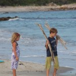 Landry Beard and  Stella Schafer gathering wood for a beach bonfire.
