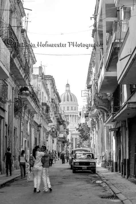 HAVANA,CUBA- FEBRUARY 21: Couple hugging and walking on the street on februrary 21, 2011 in Havana. At the end of the street you can see the Cuban capitol.