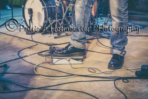 Foot of guitar player in band on music pedal