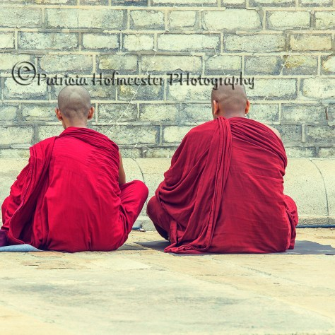 ANURADHAPURA, SRI LANKA-AUG 15: Two buddhist monks in red robes praying on the ground of the temple complex in Anuradhapura on august 15, 2013.