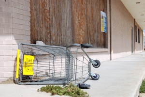 Empty Cart in front of a boarded up Dollar General store