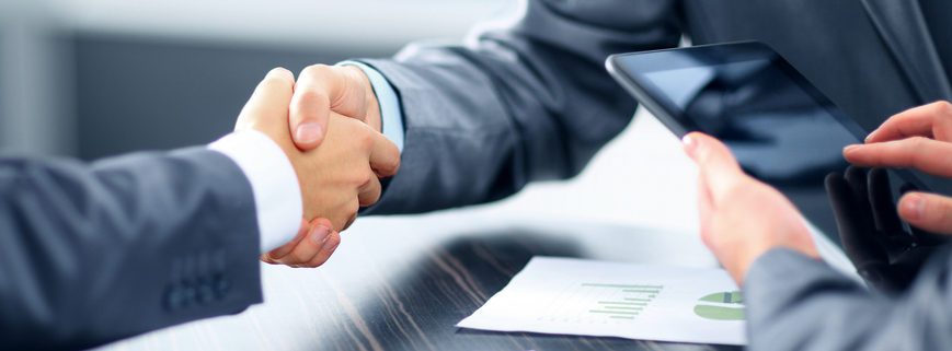 two men shaking hands over a business deal