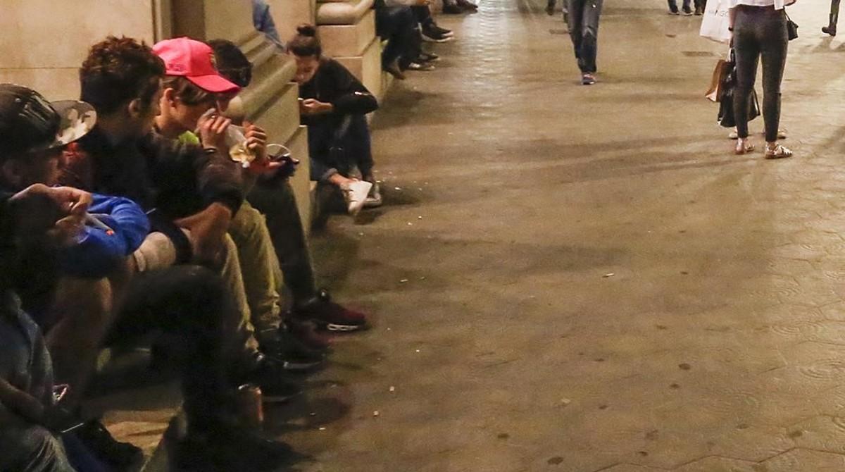 BARCELONA 24 10 2016  JOVENES MAGREBIS ESNIFANDO COLA EN LA PUERTO DE LA TIENDA APPLE DEL PASEO DE GRACIA CON PLACA CATALUNYA  FOTO DE JULIO CARBO