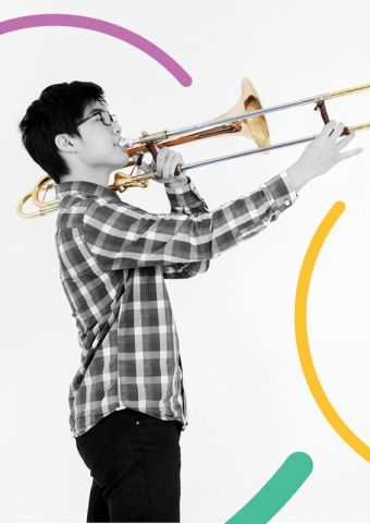 Teenager playing trumpet with swirls of colour in the background