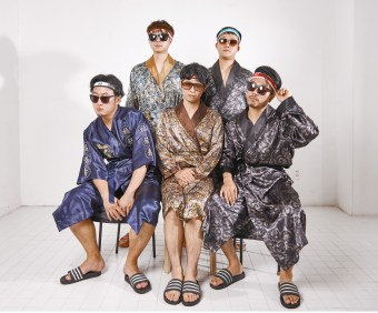 Five men sitting together in night gowns, sunglasses, headbands, and slides.