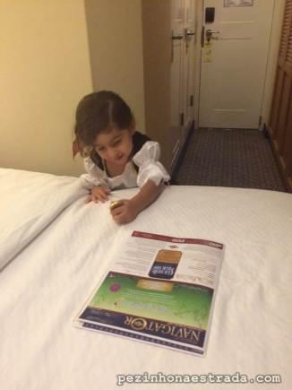 A Bela catando os chocolatinhos em formato de moeda que o Alberto deixou na cama, junto com o Personal Navigator.