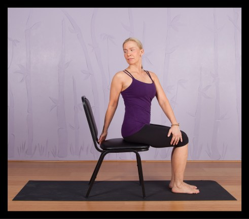 Modified Seated Spinal Twist yoga pose using a chair.