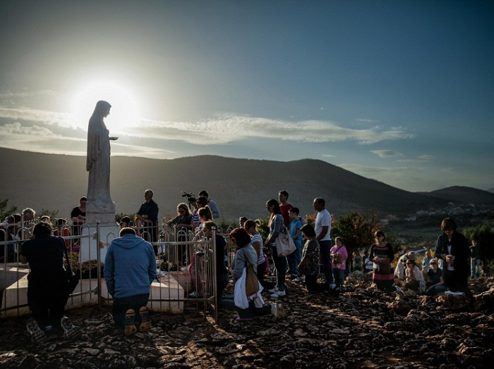 Picture of pilgrims visiting Virgin Mary statue at Medjugorje in Bosnia and Herzegovina