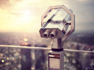 Binoculars or telescope on top of skyscraper at observation deck to admire the city skyline at sunset. Vintage effect