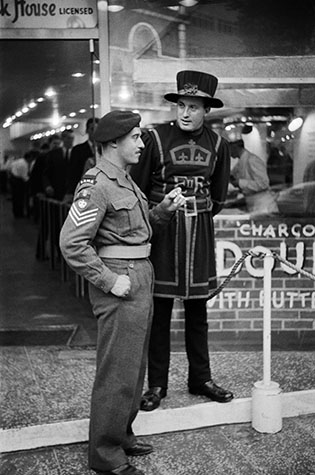 GB. England. London. Outside a hamburger joint in Leicester Square a medieval soldier employed by the fast-food chain meets his modern counterpart. 1959.