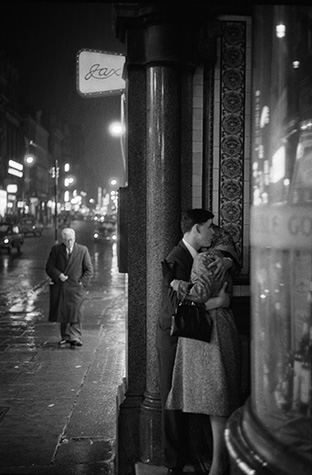 GB. England. London. A rainy night in Oxford Street where a young couple seek a tender moment in a doorway. 1960.