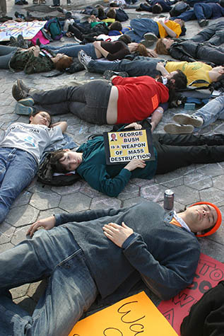USA. New York City. March 22, 2003. Demonstration against war in Iraq. Demonstrators perform a lay-in while protestors march down Broadway to Washington Square Park.