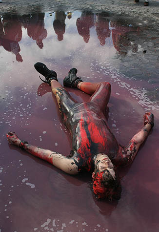 USA. New York City. March 22, 2003. Demonstration against war in Iraq. Street performer covered in blood and oil as protestors march down Broadway to Washington Square Park.