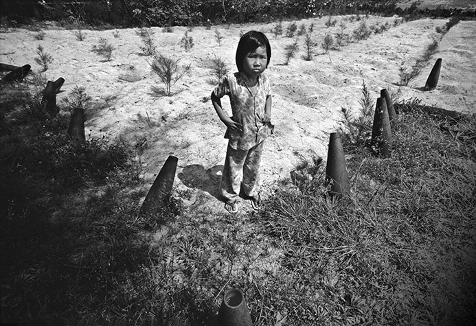 VIETNAM. Near the old American base south of Quang Tri, a young girl stands over her patch of saplings. Marked off by old artillery shells, she is responsible for their safety, warding off birds and rats. 1987