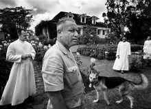 A rare moment when the constituent symbols of colonialism come together in a frame. On a French sugar plantation the owner, with his dog, guide visiting priests around the garden of his mansion. MAURITIUS. 1966
