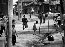 Street Scene. The Korean War had been over for fourteen years. Most of South Korea had looked much as it had for centuries. This was the main street of Sokcho, a town in North Korea before the war began-now complimented with a reminder. 1967