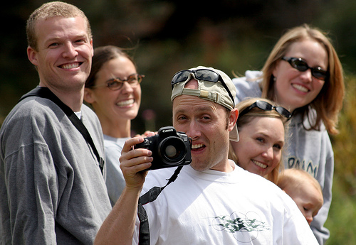 They are hiking, and taking photos of each-other. They have a few things in common.