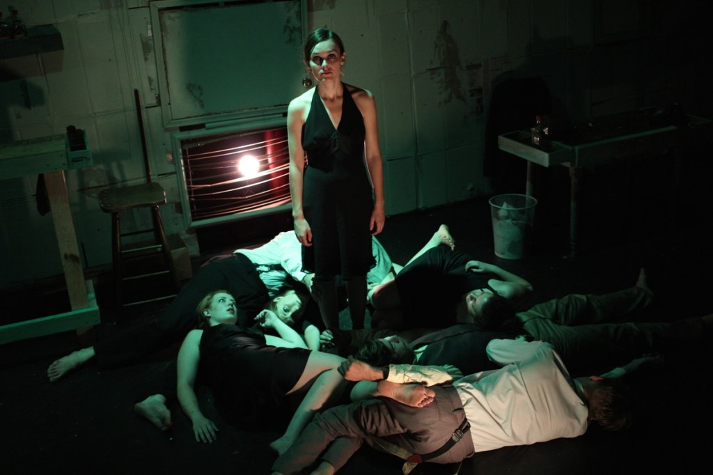 Phoebe Schaub as Charon (standing) and the ensemble of Found's CITY OF WOES