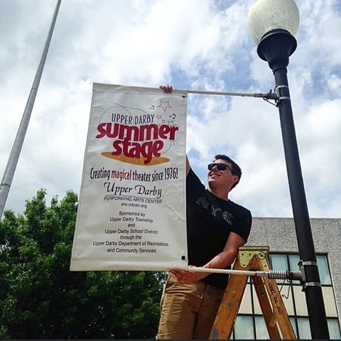 Chris Luner, Summer Stage production manager, hanging up a banner