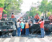Thai citizens inspect the remnants of the Thai military (กองทัพบก) equipment at Khok Wua