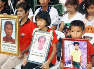 Children hold photographs of their fathers killed at Khok Wua on April 10, 2010 The names of those killed (L to R) Mr Monchai Sajung (54) Mr Boonjun Maiprasert, (#3 awaiting details)