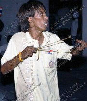 A multi-color shirt protester prepares to fire a projectile from a slingshot at red-shirt protesters in 2010