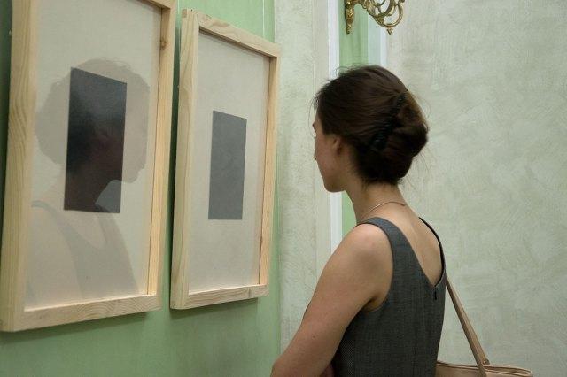 Відвідувачка розглядає картини Анни Міронової